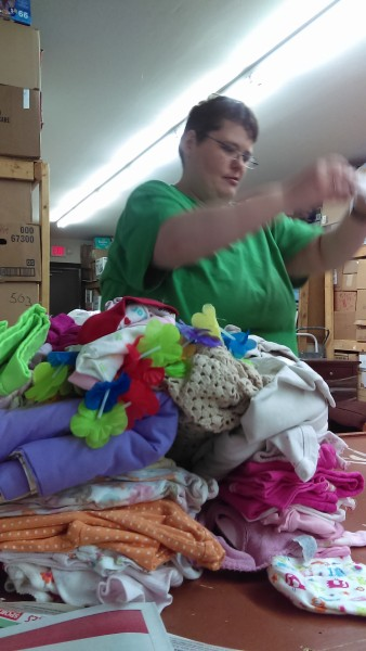 Froehler sorting through a bag of consignment items at Value Smart Retail Consignment.