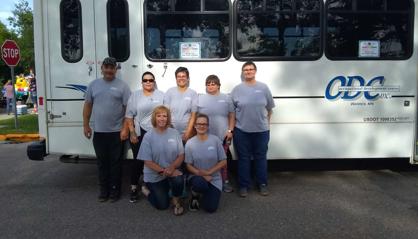 ODC staff stand outside with company bus in Warren parade