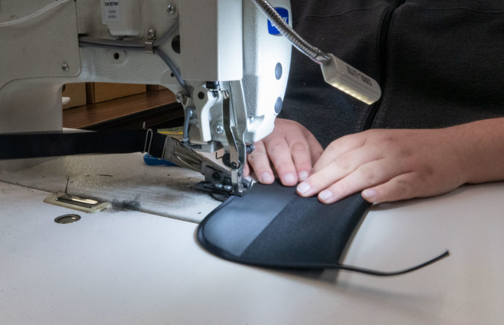 Closeup of hands sewing a tool pouch