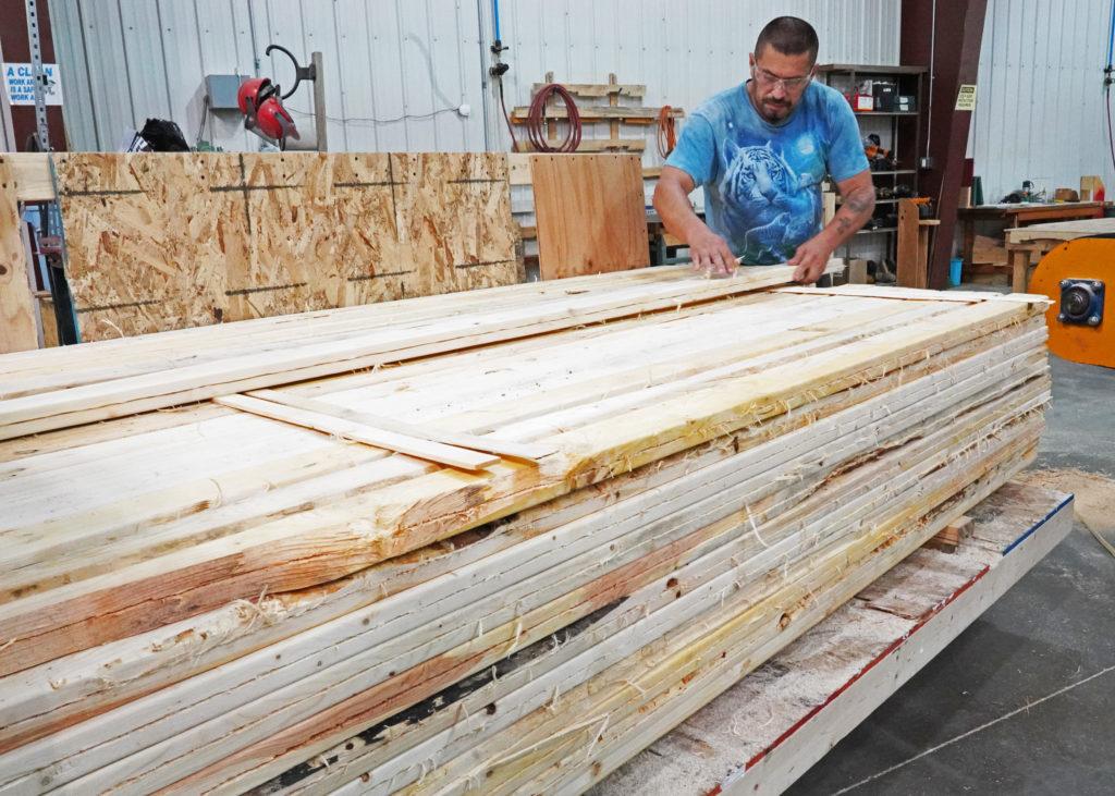 An individual stacks resawn lumber